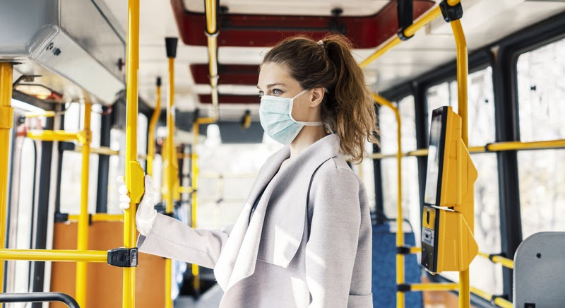 Woman wearing surgical protective mask going to work