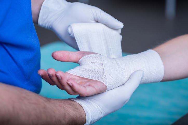 Close-up of male doctor bandaging a hand