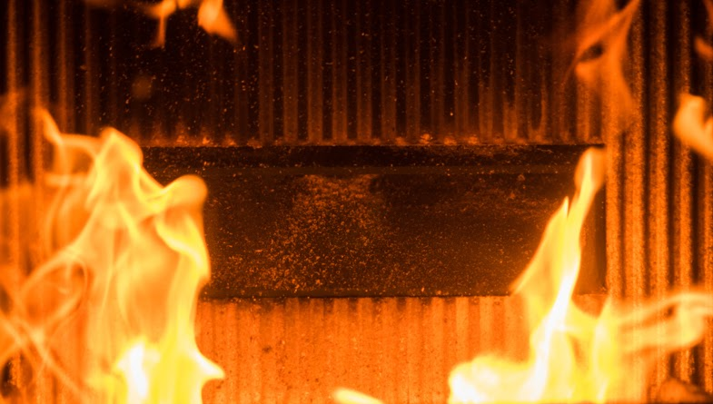 detail of burning flame in a domestic pellet burning stove with refractory brick and fuel delivery chute behind